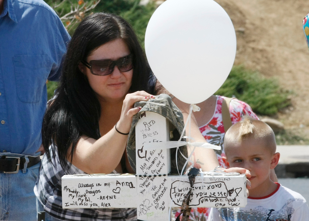 Rebecca Diercks touches the cross for family friend Air Force Staff Sergeant Jesse Childress at a impromtu memorial near the movie theater where Childress and 11 other people where killed last Friday in Aurora, Colorado July 23, 2012. REUTERS/Rick Wilking (UNITED STATES)