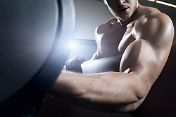 Muscular man exercising with dumbbell in fitness studio