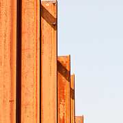 stack of orange steel girders with a white background