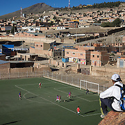 'Attitude at Altitude' Football in Potosi, Bolivia'..Locals play football on the synthetic full size pitch at Miners Stadium, high in the hills in Potosi. The stadium was paid for by miners co operatives, along with help from the President Evo Moralas and his government. 7th May 2010. Photo Tim Clayton..'Attitude at Altitude' Football in Potosi, Bolivia'..The Calvario players greet the final whistle with joyous celebration, high fives and bear hugs the players are sprayed with local Potosina beer after a monumental 3-1 victory over arch rivals Galpes S.C. in the Liga Deportiva San Cristobal. The Cup Final, high in the hills over Potosi. Bolivia, is a scene familiar to many small local football leagues around the world, only this time the game isn't played on grass but a rock hard earth pitch amongst gravel and boulders and white lines that are as straight as a witches nose, The hard surface resembles the earth from Cerro Rico the huge mountain that overlooks the town. .. Sitting at 4,090M (13,420 Feet) above sea level the small mining community of Potosi, Bolivia is one of the highest cities in the world by elevation and sits 'sky high' in the hills of the land locked nation. ..Overlooking the city is the infamous mountain, Cerro Rico (rich mountain), a mountain conceived to be made of silver ore. It was the major supplier of silver for the spanish empire and has been mined since 1546, according to records 45,000 tons of pure silver were mined from Cerro Rico between 1556 and 1783, 9000 tons of which went to the Spanish Monarchy. The mountain produced fabulous wealth and became one of the largest and wealthiest cities in Latin America. The Extraordinary riches of Potosi were featured in Maguel de Cervantes famous novel 'Don Quixote'. One theory holds that the mint mark of Potosi, the letters PTSI superimposed on one another is the origin of the dollar sign...Today mainly zinc, lead, tin and small quantities of silver are extracted from the mine by over 100 co operat