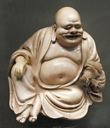 Earthenware figure of Hotei, 1800's Japanese. Budai, pronounced Hotei in Japanese, is a Chinese folklore deity. His name means 'Cloth Sack,' and comes from the bag that he carries. He is almost always shown smiling or laughing, hence his nickname in Chinese, the Laughing Buddha.