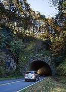Drive through solidly-built Bunches Bald Tunnel (elevation 4925 feet) at Milepost 459.3 on the Blue Ridge Parkway in North Carolina, USA. South of Soco Gap, the Parkway traverses the Eastern Cherokee Reservation and ends in the town of Cherokee. The 469-mile Blue Ridge Parkway was built 1935-1987 to aesthetically connect Shenandoah National Park (in Virginia) with Great Smoky Mountains National Park in North Carolina. (The Smokies are a subrange of the Blue Ridge Mountains, all a subset of the Appalachian Mountains.)