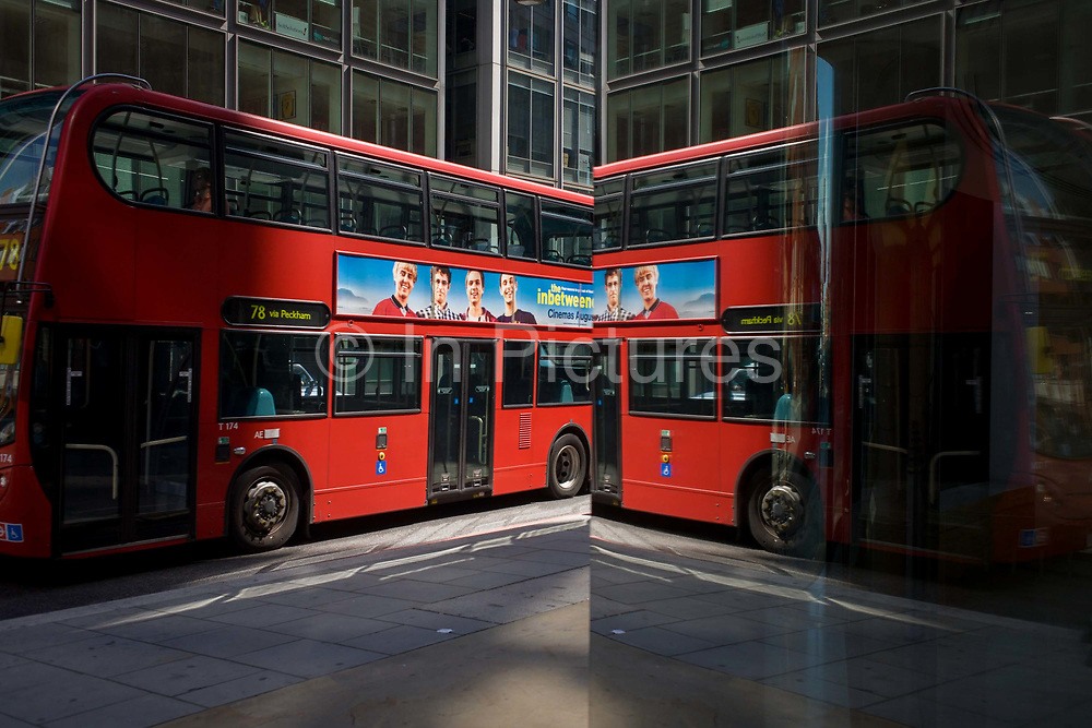 City street corner plate glass reflection of red double-decker London bus. A double image of the bus, appears as a repetition as it passes the reflective glass, its deep red paintwork reproduced against the darker corners of more office buildings in the background. The British-made film The Inbetweeners is being advertised on its side during the week of the moviels opening in cinemas.