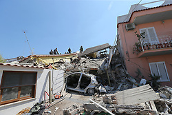 August 22, 2017 - Ischia, Italy - Rescuers team walk near a house, destroyed in the earthquake in one of the more heavily damaged areas in Casamicciola Terme, a coastal town on Ischia Island. A magnitude 4.0 earthquake struck the Italian holiday island of Ischia early this morning during peak tourist season, killing two women. The earthquake occured just two days ahead of the first anniversary of an earthquake in central Italy in which 299 people died. (Credit Image: © Marco Cantile/NurPhoto via ZUMA Press)