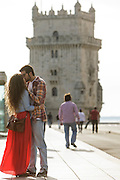 Young couple with Belém Tower on the background. The Tower was classified as a UNESCO World Heritage Site in 1983 and included in the registry of the Seven Wonders of Portugal in 2007. It was built in the early 16th century and is a prominent example of the Portuguese Manueline style.