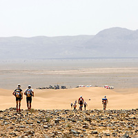 26 March 2007:  Participants run near the end of a very rocky plain just before the beginning of dunes as the bivouac is at sight during the second stage (21.7 miles) of the 22nd Marathon des Sables between Khermou and jebel El Otfal. The Marathon des Sables is a 6 days and 151 miles endurance race with food self sufficiency across the Sahara Desert in Morocco. Each participant must carry his, or her, own backpack containing food, sleeping gear and other material.