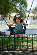 A young female Toddler aged 3 on a swing in a park. Model release available