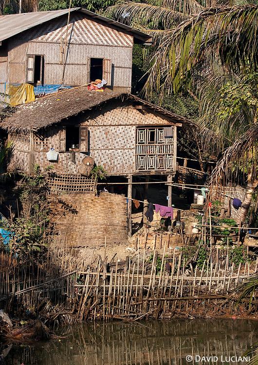Burmese huts standing along the riverbank.