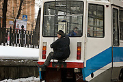Moscow, Russia, 20/02/2005..A young Russian man avoids paying his fare by riding on the outside of a tram through the speeding city traffic.