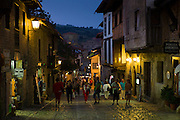 Tourists stroll at night past medieval buildings on cobbled street of Calle Del Canton in Santillana del Mar, Cantabria, Spain