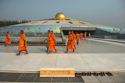 Buddhist monks gather together for the annual mass inauguration of new monks at the Wat Phra Dhammakaya, a Buddhist temple in Khlong Luang District, Pathum Thani Province north of Bangkok, Thailand. It is the centre of the Dhammakaya Movement, a Buddhist sect founded in the 1970s and led by Phra Dhammachayo.This part of the complex resembles a spaceship.