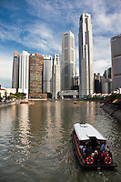 Old shophouses in Singapore line the Singapore River with modern skyscrapers sitting just behind them, providing for a unique skyline.