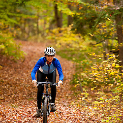 A woman mountain biking on a trail on Millstone Hill in Barre, Vermont.  Abandoned granite quarry.  Fall. Millstone Trail Association.