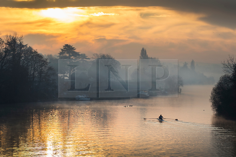 © Licensed to London News Pictures. 28/12/2016. London, UK. A rowing pair pass Hampton Court on the River Thames at first light. A very cold start to the day in some parts of the UK with temperatures well below freezing at dawn. Photo credit: Peter Macdiarmid/LNP