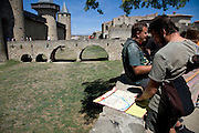 tourist studying his map while visiting La Cite in Carcassonne France