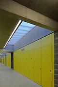 Hackney Marshes Centre by Stanton Williams Architects. Concrete interior corridor with concrete beams and yellow wall and cupboards