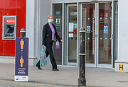 22nd February, Cheltenham, England. A shopper walking through past Santander in the town centre during England's third national lockdown.
