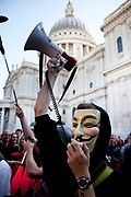 "Masked protester outside St Pauls Cathedral with a megaphone at the Occupy London protest, October 15th 2011. Protest spreads from the US with this demonstrations in London and other cities worldwide. The 'Occupy' movement is spreading via social media. After four weeks of focus on the Wall Street protest, the campaign against the global banking industry started in the UK this weekend, with the biggest event aiming to ""occupy"" the London Stock Exchange. The protests have been organised on social media pages that between them have picked up more than 15,000 followers. Campaigners gathered outside  at midday before marching the short distance to Paternoster Square, home of the Stock Exchange and other banks.It is one of a series of events planned around the UK as part of a global day of action, with 800-plus protests promised so far worldwide.Paternoster Square is a private development, giving police more powers to not allow protesters or activists inside."