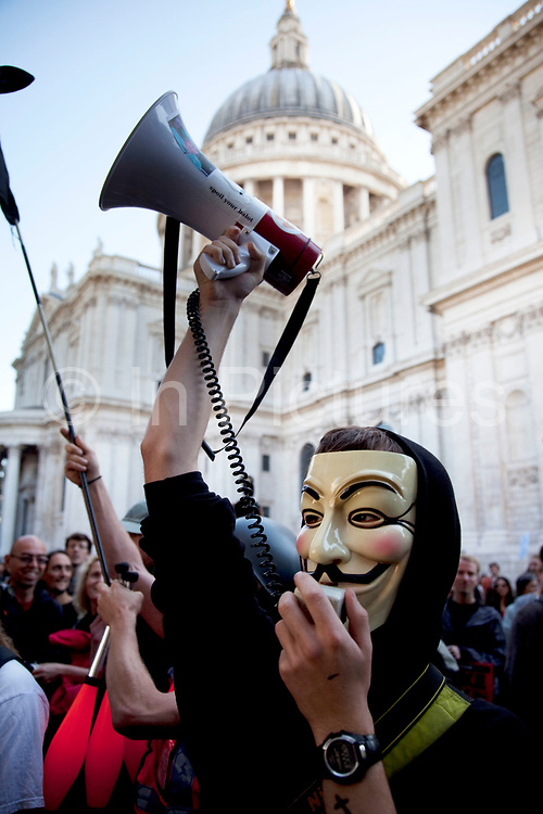 """Masked protester outside St Pauls Cathedral with a megaphone at the Occupy London protest, October 15th 2011. Protest spreads from the US with this demonstrations in London and other cities worldwide. The 'Occupy' movement is spreading via social media. After four weeks of focus on the Wall Street protest, the campaign against the global banking industry started in the UK this weekend, with the biggest event aiming to """"occupy"""" the London Stock Exchange. The protests have been organised on social media pages that between them have picked up more than 15,000 followers. Campaigners gathered outside  at midday before marching the short distance to Paternoster Square, home of the Stock Exchange and other banks.It is one of a series of events planned around the UK as part of a global day of action, with 800-plus protests promised so far worldwide.Paternoster Square is a private development, giving police more powers to not allow protesters or activists inside."""