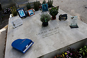 """Decorated grave for singer and actor Gilbert Becaud, in the Pere Lachaise cemetery, Paris. Gilbert Bécaud (1927 – 2001 was a French singer, composer and actor, known as """"Monsieur 100.000 Volts"""" for his energetic performances. His best-known hits are """"Nathalie"""" and """"Et Maintenant"""", a 1961 release that became an English language hit as """"What Now My Love"""". He remained a popular artist for nearly fifty years, identifiable in his dark blue suits, with a white shirt and """"lucky tie""""; blue with white polka dots. Père Lachaise Cemetery (French: Cimetière du Père-Lachaise- or officially cimetière de l'Est, """"East Cemetery"""") is the largest cemetery in the city of Paris, France (44 hectares (110 acres) containing the remains of a million French and foreign dead."""