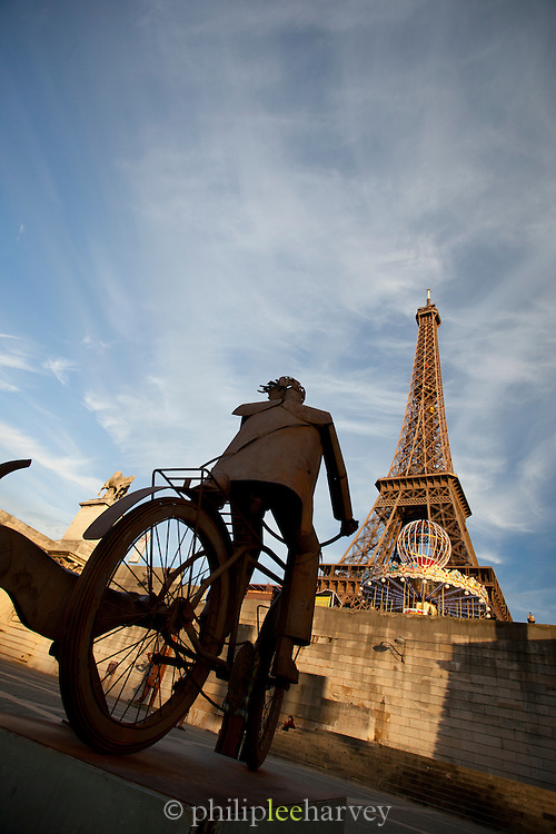 A modern art sculpture in front of the iconic Eiffel Tower in Paris, France