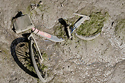 A fly-tipped Santander rental bike lies in low-tide mud of the River Lea in Canning Town, Newham, on 11th August 2021, in London, England.