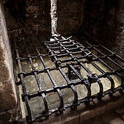 A black metal grill covers the original water well at Caernarfon Castle in northwest Wales. A castle originally stood on the site dating back to the late 11th century, but in the late 13th century King Edward I commissioned a new structure that stands to this day. It has distinctive towers and is one of the best preserved of the series of castles Edward I commissioned.