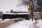 08 FEBRUARY 2021 - DES MOINES, IOWA: Traffic waits for a snow covered train to pass in downtown Des Moines. Central Iowa, including Des Moines, is enduring its coldest winter in 25 years. Daily high temperatures this week are not expected to go above 10F (-12C) and nightly lows are expected to be about -5F (-20C). In addition to the cold weather, this is the second snowiest winter in Des Moines history. So far this winter there has been more than 44 inches (111 centimeters) of snow. Des Moines normally gets about 35 inches (90 centimeters) of snow all winter.        PHOTO BY JACK KURTZ