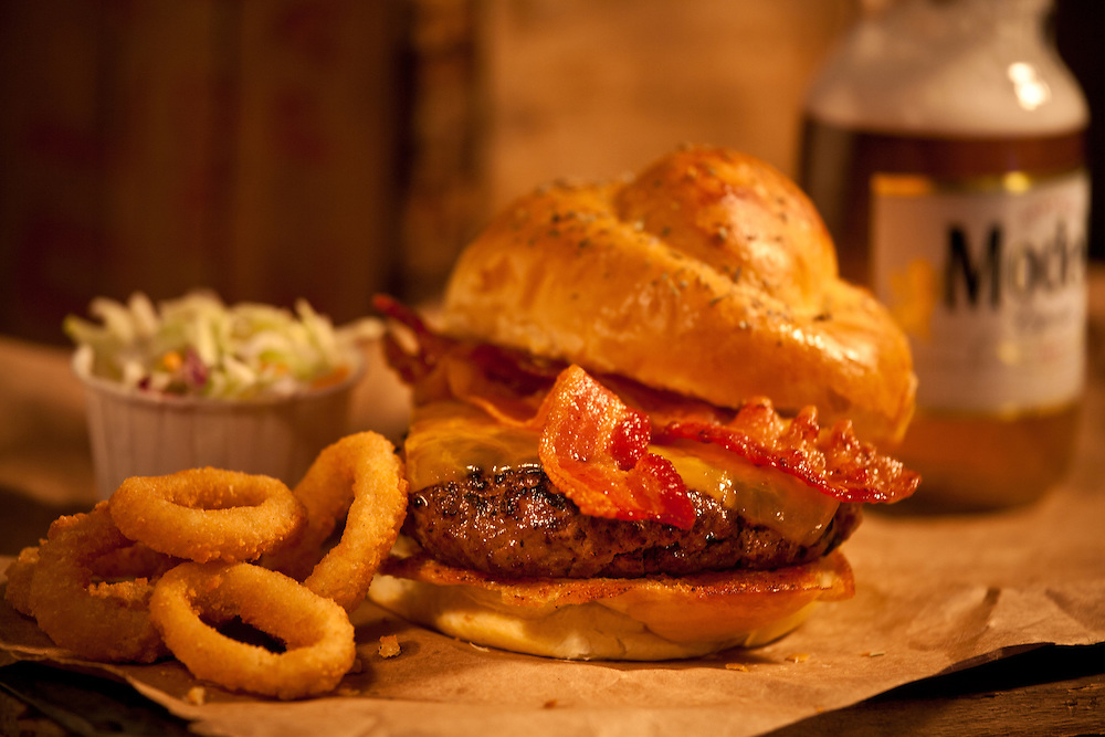 Bacon Ceddar Cheeseburger,with onion rings and cold slaw and beer,sitting on brown paper on top of old crates