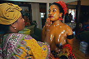 On the final day of her ngasech, the traditional first childbirth ceremony, a young mother in Palau, Micronesia, is dressed up and anointed with cocnut oil and turmeric by a medicine woman. Practically every Palauan woman goes through the ngasech ceremony, begun one to three months after she has given birth to her first child. The ceremony consists of hot baths, taken twice daily for five to ten days, depending on the clan of the new mother, and then a sweat bath on the day of her coming out ceremony when she is dressed up and shown to the family of the father of her child. The purpose of the baths is to heal her skin, remove stretch marks and blemishes, and also to clean the inside of her private parts.