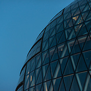 Part of the London City Hall building against the sky at dusk.