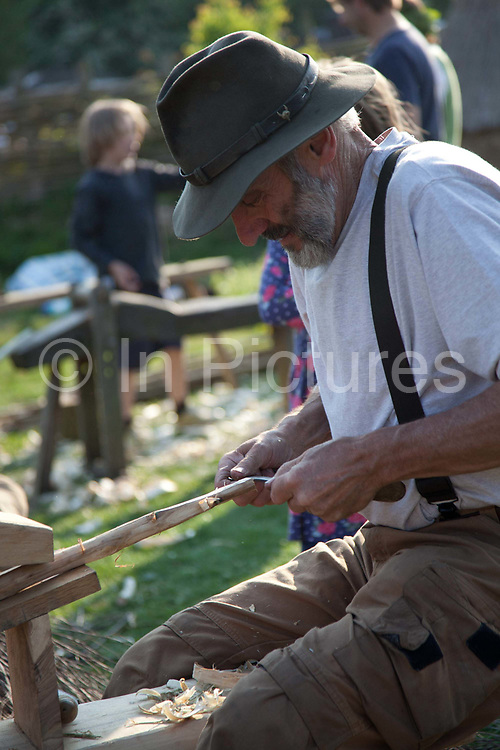 A man making wood carvings in a community demonstration outdoors. The annual Beltane celebrations at Butser ancient farm, Hampshire, marking the beginning of the British summer.