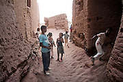 Children play in the sandy passageways of Ait Bounou, an ancient kasbah, or fortified village, in the Moroccan Sahara. The town is quickly falling into ruin as the inhabitants flee the drying well and the advancement of the dunes expedited by a 16-year drought and the damming of the Draa River.