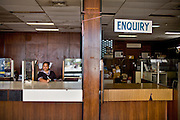 "In 1995, following the collapse of the Bank of Nauru, the country found itself facing a serious financial crisis. There are currently no Bank on Nauru and it's a cash only economy..Calmina waits for customers at the former Bank of Nauru, now the government's ""Department of Payment""...During the 1990s, it was possible to establish a licensed bank in Nauru for only $25,000 with no other requirements. ..Nauru, officially the Republic of Nauru is an island nation in Micronesia in the South Pacific.  Nauru was declared independent in 1968 and it is the world's smallest independent republic, covering just 21 square kilometers..Nauru is a phosphate rock island and its economy depends almost entirely on the phosphate deposits that originate from the droppings of sea birds. Following its exploitation it briefly boasted the highest per-capita income enjoyed by any sovereign state in the world during the late 1960s and early 1970s..In the 1990s, when the phosphate reserves were partly exhausted the government resorted to unusual measures. Nauru briefly became a tax haven and illegal money laundering centre. From 2001 to 2008, it accepted aid from the Australian government in exchange for housing a Nauru detention centre, with refugees from various countries including Afghanistan and Iraq..Most necessities are imported on the island..Nauru has parliamentary system of government. It had 17 changes of administration between 1989 and 2003. In December 2007, former weight lifting medallist Marcus Stephen became the President."