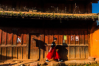 A Chinese woman walks along the street in the market town of Shaxi, on the Tea Horse Caravan Road, which links Southern Yunnan to Tibet and Burma and retains its position as one of the best preserved historic market hubs today. Yunnan Province, China.