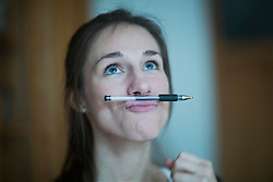 Young woman holding pen between nose and lips, Freiburg im Breisgau, Baden-Wuerttemberg, Germany