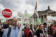 """Participants in """"The March For Life"""" are seen carrying  crosses and banners as they march in front of the Bundestag in Berlin's Mitte district, on September 16, 2017. In the center of the pro-life event was the call by the organizers for German politicians and society to take active action against a """"silent increase of acceptance"""" of the phenomenon. Abortion in Germany is permitted in the first trimester of the pregnancy, with the condition of mandatory counseling and in a later period of the pregnancy in cases of medical necessity.<br /> (Photo by Omer Messinger)"""
