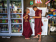 21 MAY 2013 - MAE KU, TAK, THAILAND:  Burmese Buddhist novice monks buy an ice cream treat in a Thai owned convenience store in Mae Ku, Thailand. There are more than two million Burmese migrants and refugees in Thailand and the overwhelming majority do not have access to Thai social services so they use services provided by NGOs. The Wangpha Clinic is run by the Shaklo Malaria Research Unit (SMRU), which operates clinics along the Thai-Burma (Myanmar) border in Tak province.    PHOTO BY JACK KURTZ