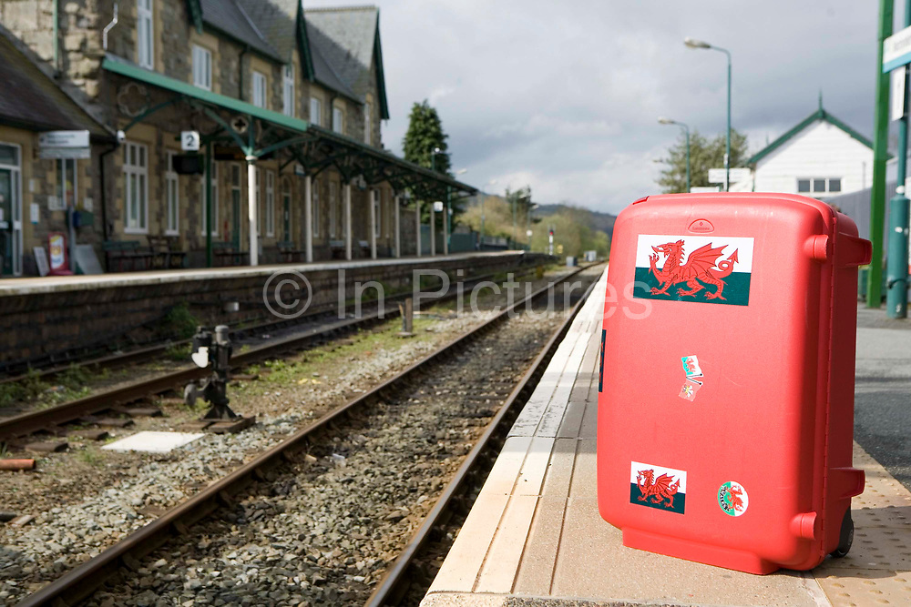 A Welsh red suitcase sitting on the platform at Machynlleth town railway station, Wales.