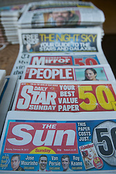 © licensed to London News Pictures. London, UK 26/02/2012. The Sun on Sunday's first edition is pictured with some other Sunday newspapers on a newsagent's desk in central London, this morning (26/02/12). Photo credit: Tolga Akmen/LNP