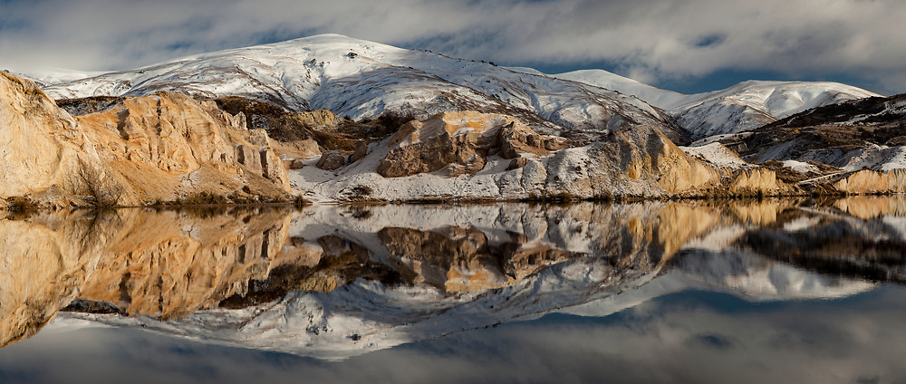 Blue lake reflection panorama after winter snow fall, St Bathans historic gold fields township, Central Otago