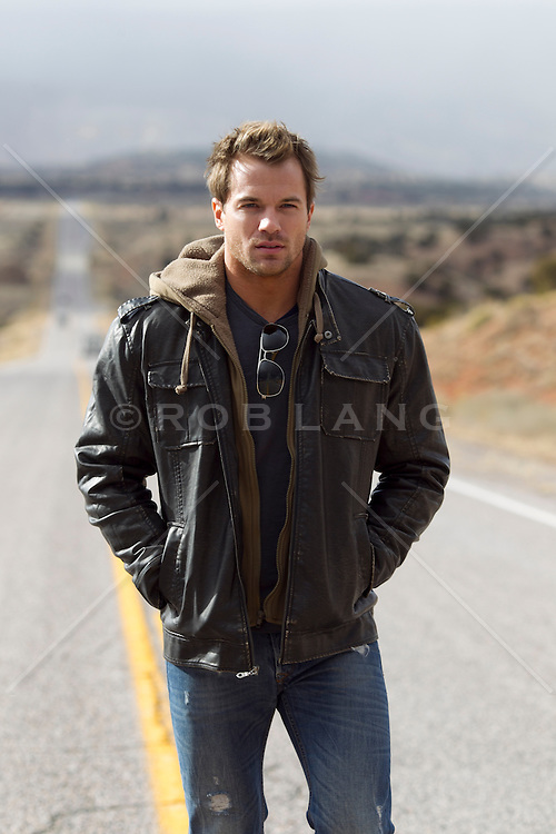 man in a leather jacket and jeans walking on an empty road in Abiquiu, New Mexico