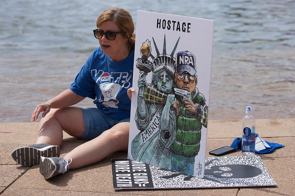 A marcher sits near a fountain and holds a sign in protest over the ongoing shootings in schools across the country during the March for Our Lives in front of Dallas City hall in downtown Dallas.