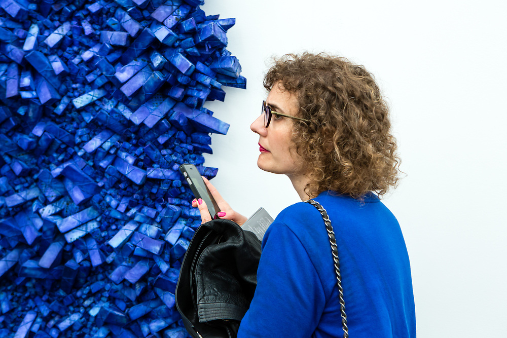 """New York, NY - 5 May 2017. The opening day of the Frieze Art Fair, showcasing modern and contemporary art presented by galleries from around the world, on Randall's Island in New York City. A woman whose sweater closely matches the color of Kwang Young Chun's piece, part of a series of """"Aggregations,"""" in the PKM Gallery from Seoul."""