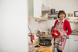 Portrait of a senior woman mixing butter in mixing bowl in kitchen, Munich, Bavaria, Germany
