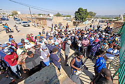 JOHANNESBURG, SOUTH AFRICA - MAY 08: People gathering at a food distribution centre in Diepsloot on May 08, 2020 in Diepsloot, South Africa. In partnership with with government and Celebration Church, Engen Fuel Retailers contributed food parcels for over 4000 familes in Diepsloot during lockdown level 4. (Photo by Dino Lloyd)