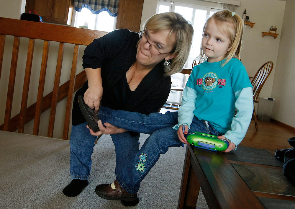 Barb Kotzian (L) helps daughter Avery into her shoes at their home in Thornton, Colorado March 25, 2010.  Barb is a achondroplasia dwarf, a rare genetic disorder of bone growth but daughter Avery is average sized.  Preferring to be called little persons Barb is active in the Little People of America, the only dwarfism support organization that includes all 200+ forms of dwarfism.  REUTERS/Rick Wilking (UNITED STATES)