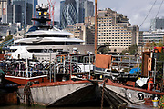 With heritage barges and lighters in the foreground, the superyacht Kismet dominates the river Thames, on 20th October 2021, in London, England. Kismet is a 95.2m 312 ft-long superyacht which was built in 2014. It is managed by the Moran Yacht & Ship chartering business, and is owned by Pakistani-American billionaire Shahid Khan. Tower Bridge Moorings is the capital's only floating gardens - a sustainable way of living for a community of more than one hundred adults and children, and a shelter for wildlife on the river. Tower Bridge Moorings is the capital's only floating gardens - a sustainable way of living for a community of more than one hundred adults and children, and a shelter for wildlife on the river.