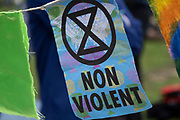 Extinction Rebellion logo and non violent slogan at the Marine Rebellion march on 6th September 2020 in London, United Kingdom. Ocean Rebellion, Sea Life Extinction, Animal Rebellion and Extinction Rebellion joined together to celebrate the biodiversity found in our seas, and to grieve at the destruction of the Earth's oceans and marine life due to climate breakdown and human interference, and the loss of lives, homes and livelihoods from rising sea levels. Extinction Rebellion is a climate change group started in 2018 and has gained a huge following of people committed to peaceful protests. These protests are highlighting that the government is not doing enough to avoid catastrophic climate change and to demand the government take radical action to save the planet.