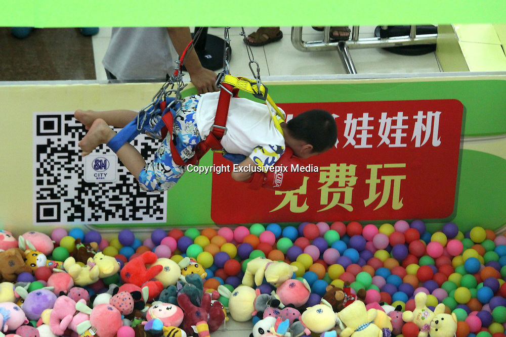 CHONGQING, CHINA - AUGSUT 07: (CHINA OUT) <br /> <br /> Human Claw Machine Opens At Chongqing Shopping Mall <br /> <br /> A child grabs toys acting as a claw after buckling  up on a human claw machine at a shopping mall  in Chongqing, China.<br /> ©Exclusivepix Media
